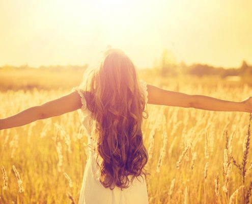 Girl with arms outstretched in nature | embracing life's challenges